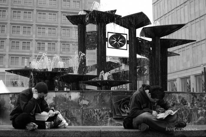 """Liebhaber guter Literatur genießen ihre Lektüre unter den Wassersäulen der """"Nuttenbrosche"""" auf dem Alexanderplatz."""