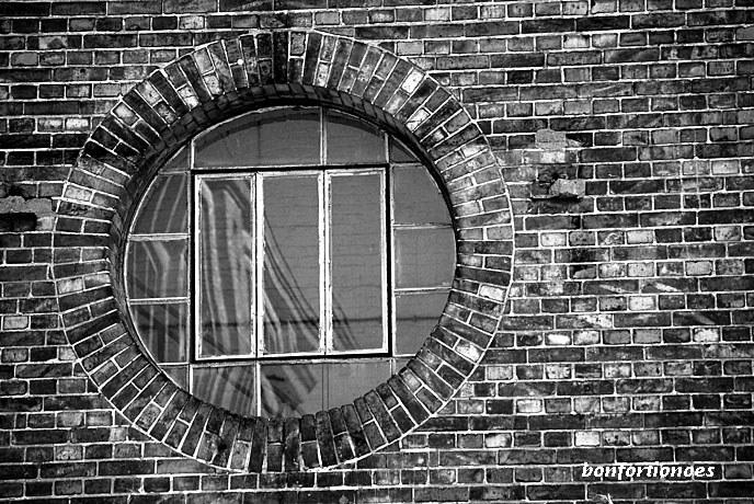Kreisrund sticht das gläserne Auge zwischen den Backsteinen hervor. Wie in einem Kameraobjektiv sich in ihm die massiven Ziegelmauern der umstehenden Fabrikgebäude. Direkt an der Spree gelegen, ist die Köpenicker Glanzfilmfabrik in einem Dornröschenschlaf versunken. Das vom amerikanischen Kodak-Konzern übernommene Unternehmen ist eine der Wiegen der Filmindustrie hierzulande.