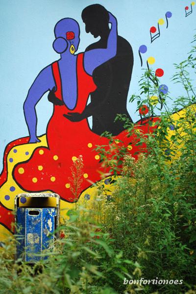 Vielfarbige Töne und flammende Leidenschaft hinter Spontanvegetation: Kiez-Flamenco! Gesehen an einer Hauswand in der Waldemarstraße.